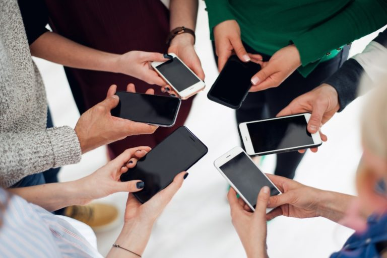 Group of people holding smartphones in a huddle