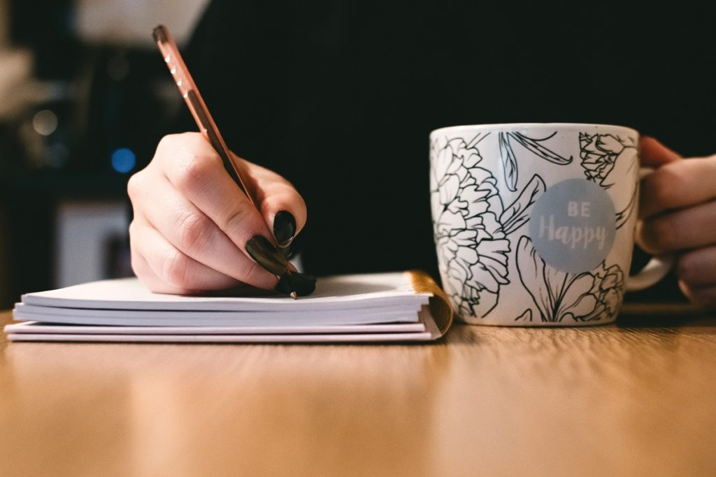 person holding a mug while writing on a notebook