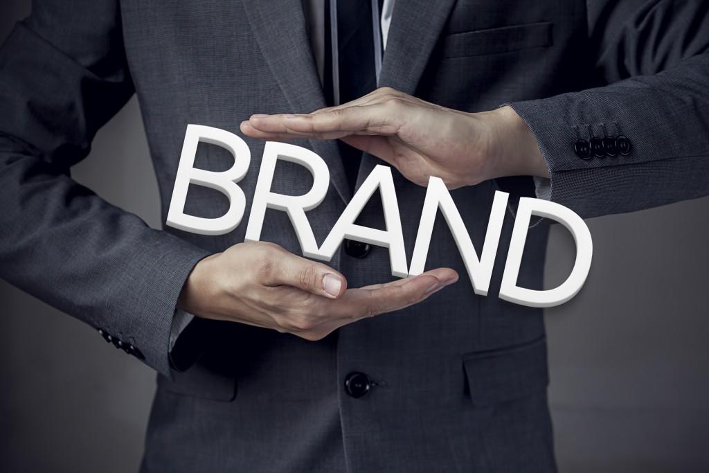 businessman holding a brand text
