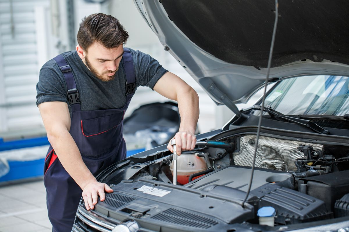 mechanic working on the engine bay of a car