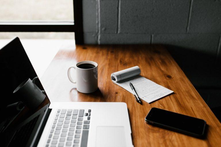 coffee notepad laptop on wooden desk