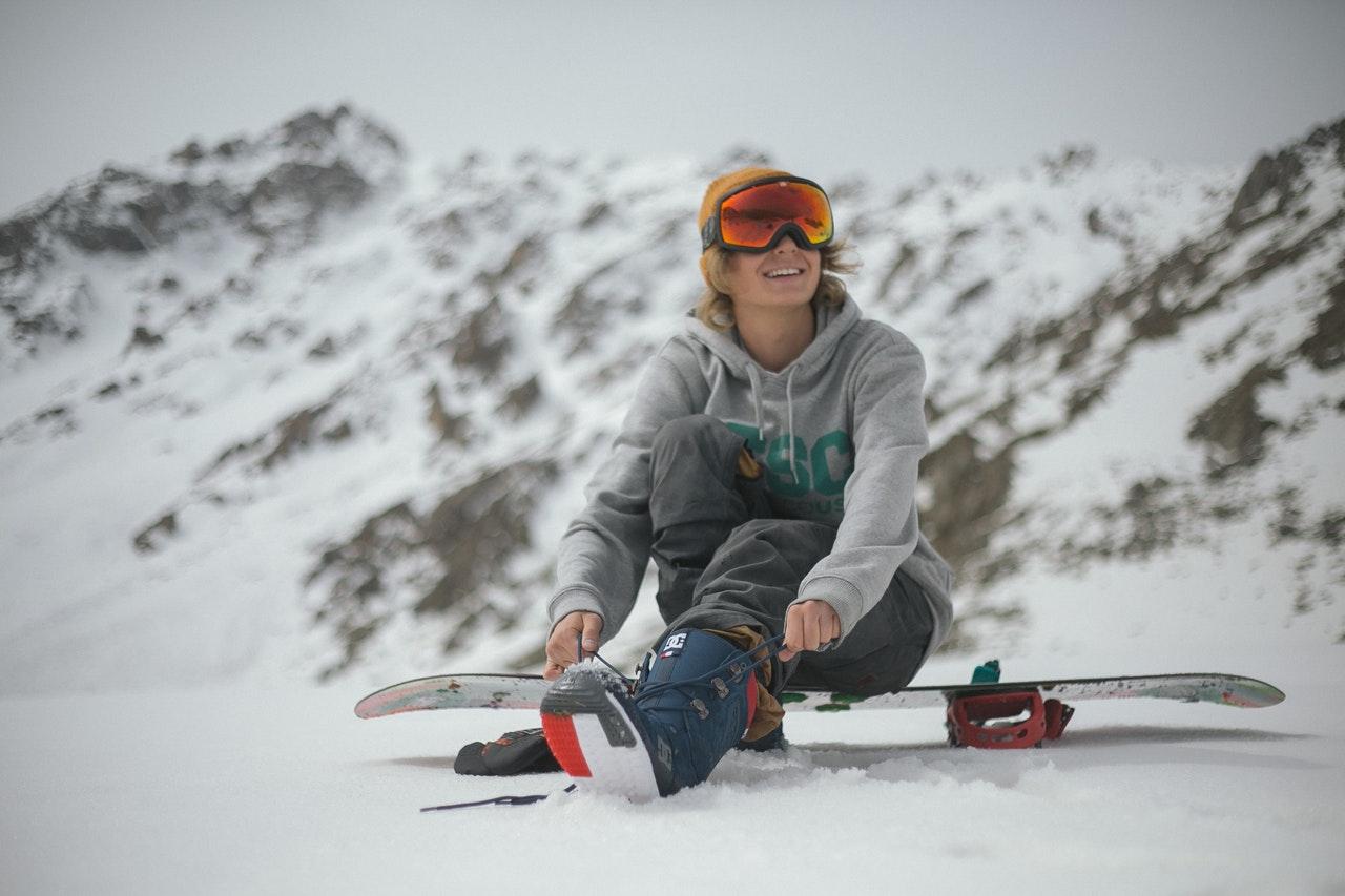 man sitting on his snowboard