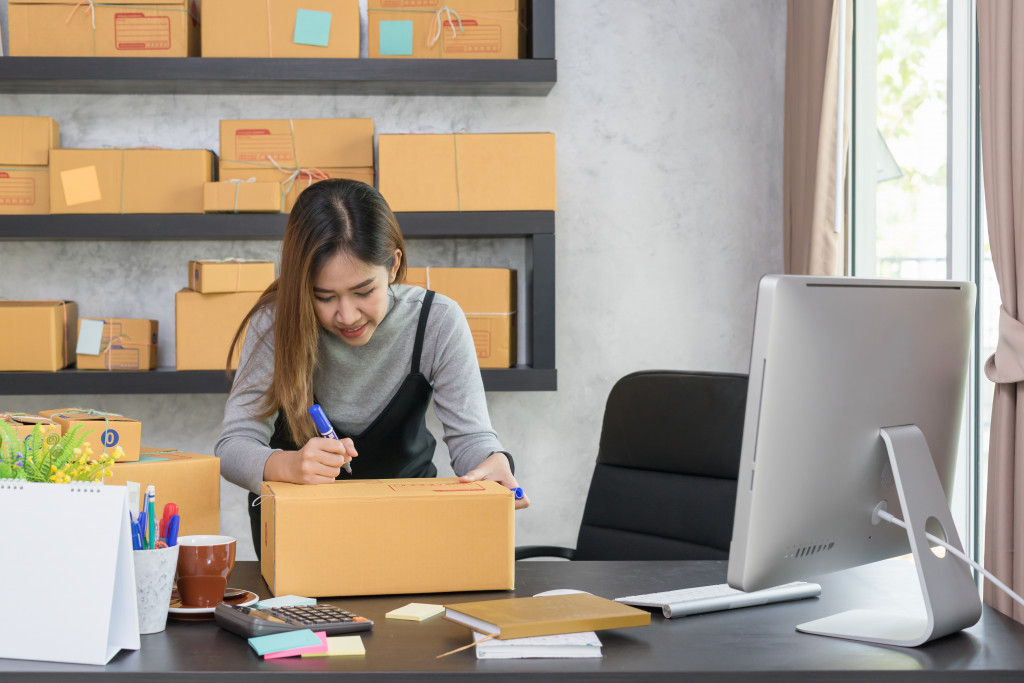 woman writing on box for delivery